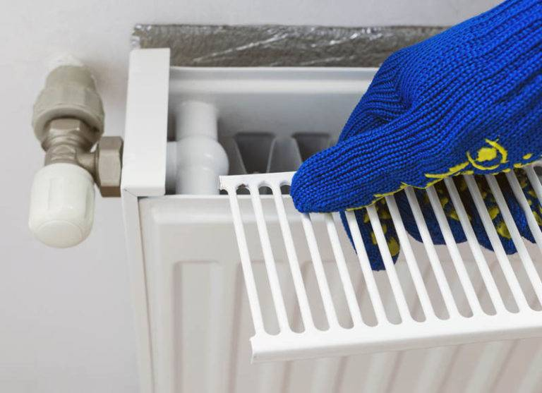 gas engineer opening grill on top of home radiator