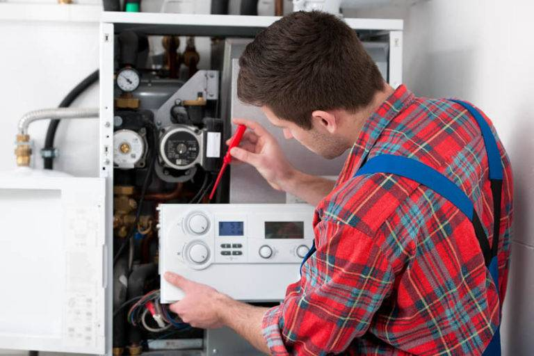 man working on inside of boiler