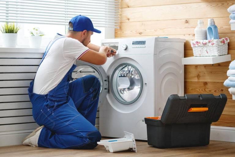 plumber working on washing machine pipes